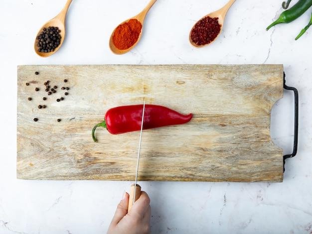 Vrouw hand snijden peper op snijplank en kruiden op witte tafel