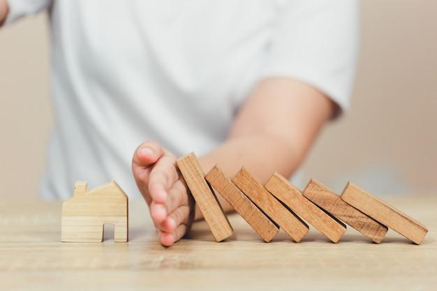 Vrouw hand stoppen risico dat de houten blokken vallen op huis.
