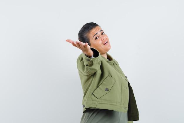 Vrouw hand uitrekken terwijl poseren in jas, t-shirt