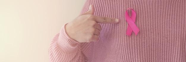Vrouw hand wijzend op roze lint