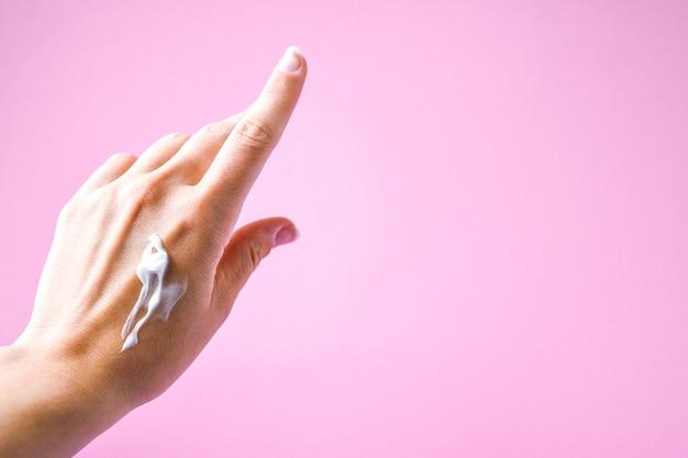 Vrouw handcrème toe te passen op kleur achtergrond, crème bij de hand