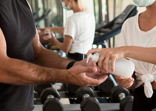 Vrouw handdesinfecterend middel geven aan de mens in de sportschool