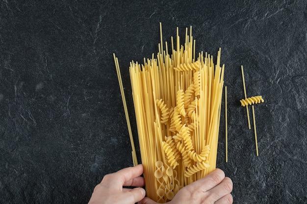 Vrouw handen aanraken van verschillende pasta op donkere ondergrond.
