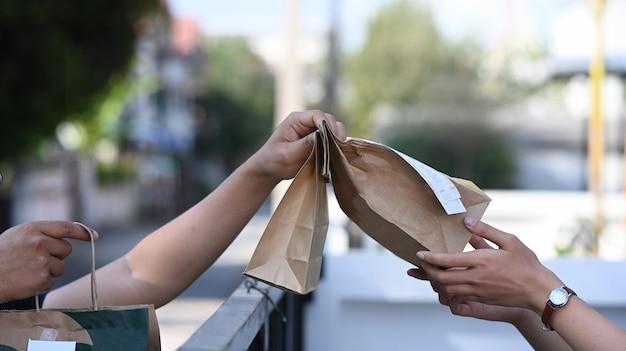 Vrouw handen accepteren papieren zak met eten van bezorger bij deuropening.