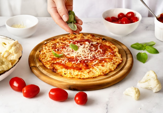 Vrouw handen besprenkelen verse basilicum bladeren op de top van bloemkool pizza