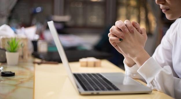 Vrouw handen bidden met laptop thuis Premium Foto