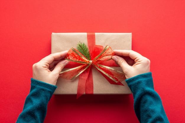 Vrouw handen binden een boog op kerstcadeau op rood