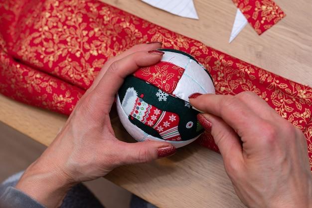 Vrouw handen close-up shot snijdt rode stof met een schaar, en het maken van decoraties.