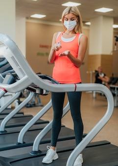 Vrouw handen desinfecteren alvorens fitnessapparatuur te gebruiken