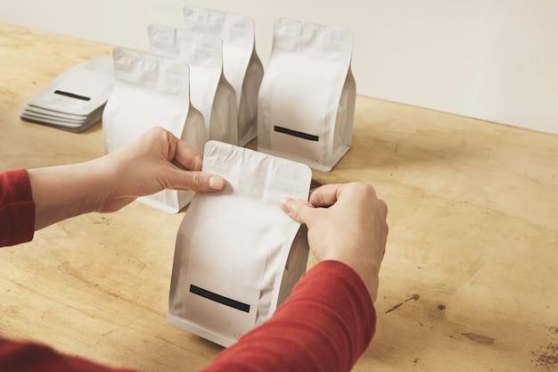 Vrouw handen getly verzegelen lege bulkverpakkingen