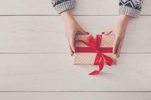 Vrouw handen geven verpakte kerst of andere handgemaakte vakantie cadeau in papier met rood lint