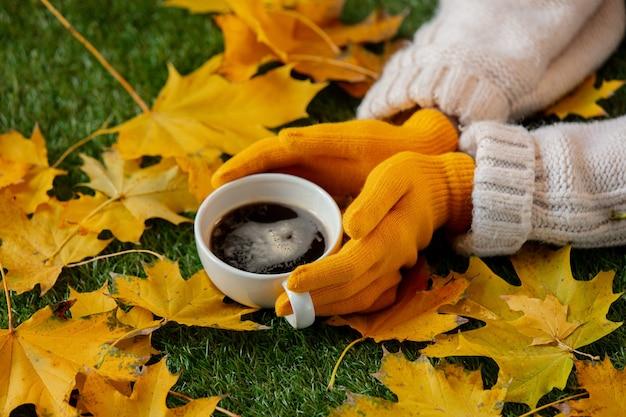 Vrouw handen houden een kopje koffie naast gele esdoorn bladeren op een groen gras