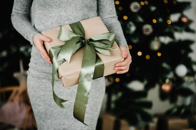 Vrouw handen houden kerstcadeau of nieuwjaar versierde geschenkdoos. afgezwakt beeld. prettige kerstdagen en fijne feestdagen. detailopname.