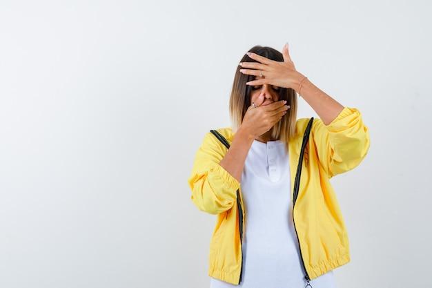 Vrouw handen houden op mond en voorhoofd in t-shirt, jasje en op zoek bedroefd, vooraanzicht.