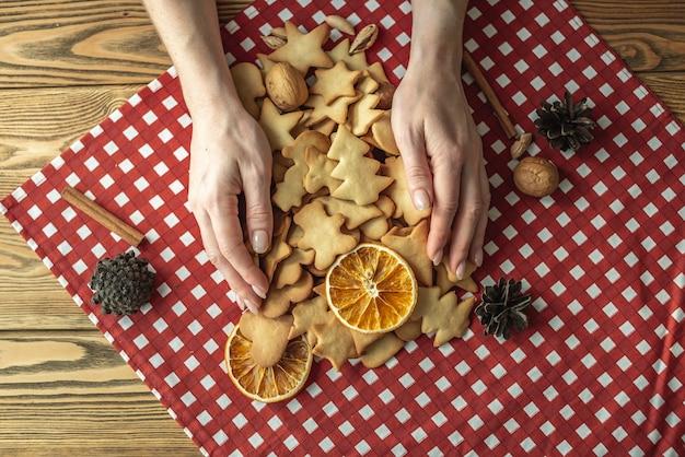 Vrouw handen houden zelfgemaakte koekjes op het rode tafellaken op een houten tafel