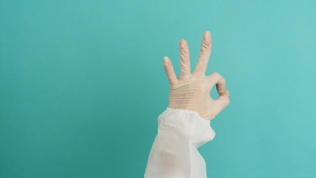 Vrouw handen in ppe-pak en medische handschoenen doet a ok (okey) handteken op blauw en groen of tiffany blue achtergrond.