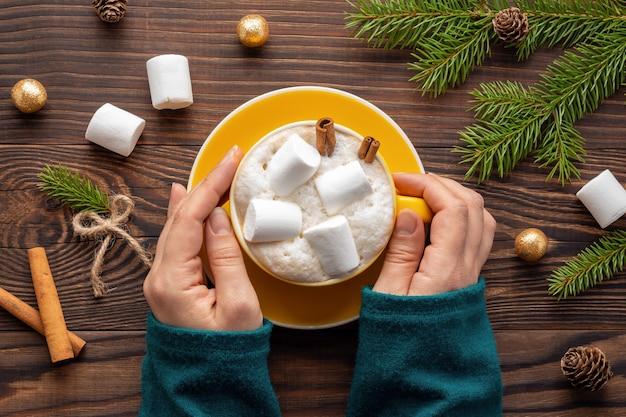 Vrouw handen in trui houden een kopje latte met marshmallows op houten tafel
