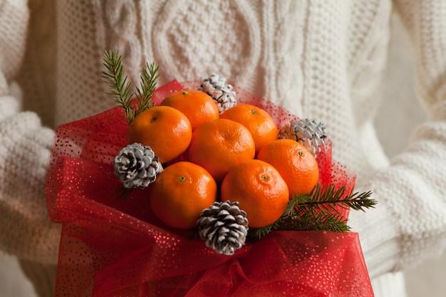 Vrouw handen in witte trui met boeket mandarijnen en kerstboom takken. eetbaar nieuwjaarsboeket van fruit. cadeau voor kerstmis. doe-het-zelf cadeau. nuttig geschenk gemaakt van fruit. decor van fruit.