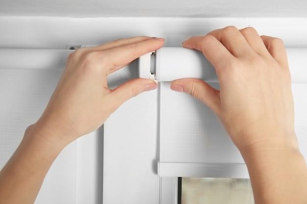 Vrouw handen installeren jaloezieën, close-up