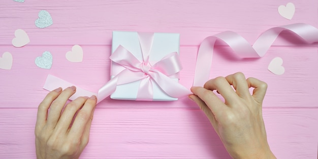 Vrouw handen inwikkeling boog op geschenkdoos met papieren harten