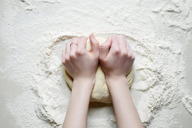 Vrouw handen kneedt het deeg met bloem op de witte keukentafel. bovenaanzicht plat leggen.