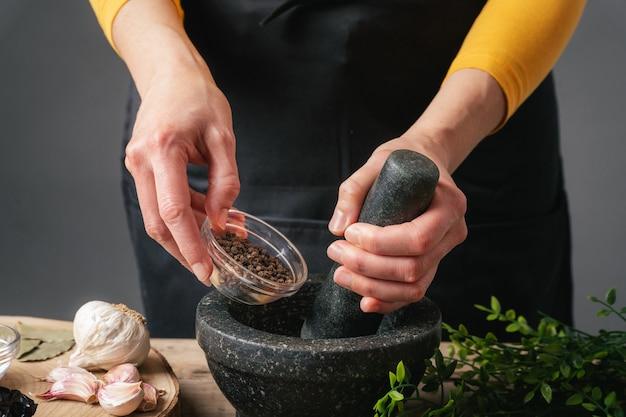Vrouw handen koken gieten peper in mortel