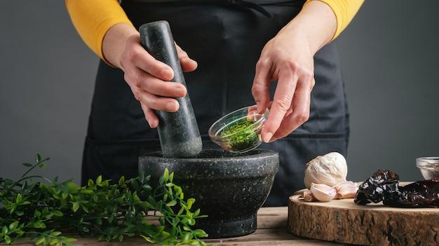 Vrouw handen koken peterselie gieten in de mortel