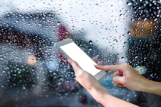 Vrouw handen met behulp van mobiele slimme telefoon met op regen druppel bij glazen raam met stad