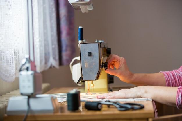 Vrouw handen met behulp van naaimachine op een naaien fabricage, naaiproces