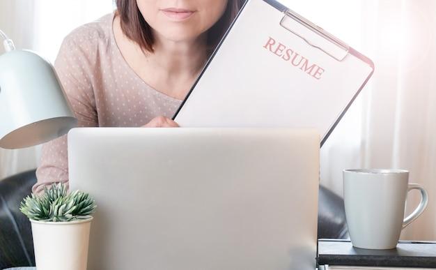 Vrouw handen met cv-applicatie in de buurt van haar werkplek met laptop.