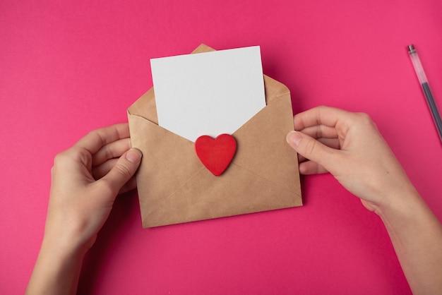 Vrouw handen met de ambachtelijke envelop met een blanco vel en rood hart. valentijnsdag concept.