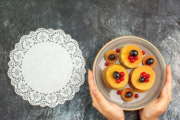 Vrouw handen met dienblad met pannenkoek ontbijt en ingericht servet
