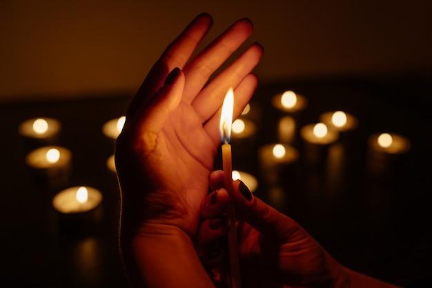 Vrouw handen met een brandende kaars. veel kaarsvlammen gloeien. detailopname.