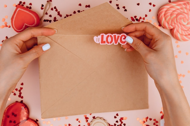 Vrouw handen met een brief in ambachtelijke envelop op de roze achtergrond. en stopt het woord liefde in een envelop. valentijnsdag concept.