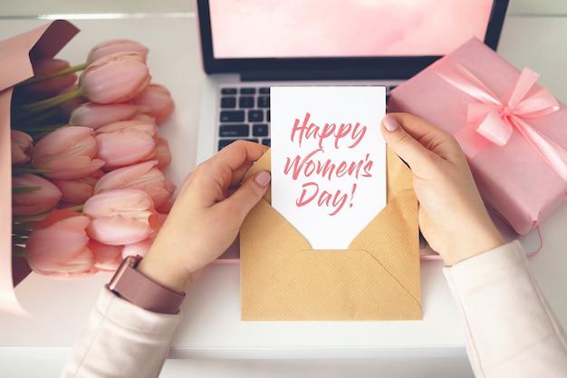 Vrouw handen met een brief in ambachtelijke envelop. roze achtergrond, vrouwendag concept. tulpenbloem en roze geschenkdoos op de achtergrond. thuis bureau voor dames.