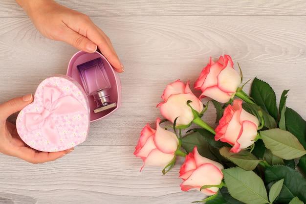 Vrouw handen met een geschenkdoos in hartvorm met parfum over grijze houten achtergrond met mooie rozen. concept van het geven van een geschenk op vakantie. bovenaanzicht.
