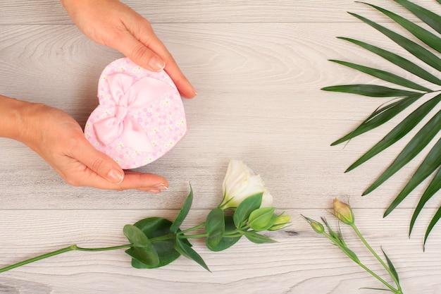 Vrouw handen met een geschenkdoos in hartvorm over grijze houten achtergrond met prachtige bloemen en groene bladeren. concept van het geven van een geschenk op vakantie. bovenaanzicht.