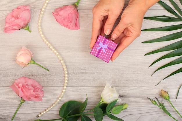 Vrouw handen met een geschenkdoos op grijze houten achtergrond met prachtige bloemen en groene bladeren. concept van het geven van een geschenk op vakantie. bovenaanzicht.
