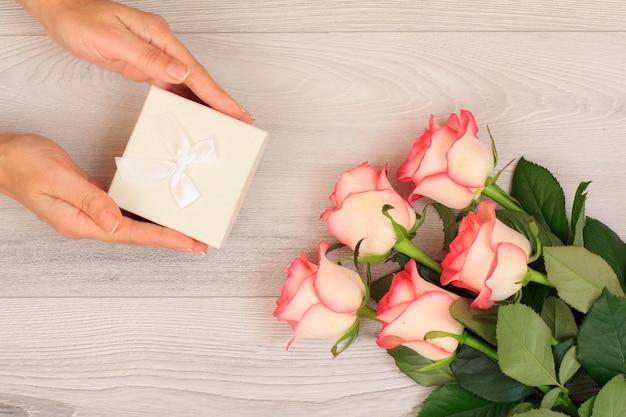 Vrouw handen met een geschenkdoos over grijze houten achtergrond met mooie rozen. concept van het geven van een geschenk op vakantie. bovenaanzicht.