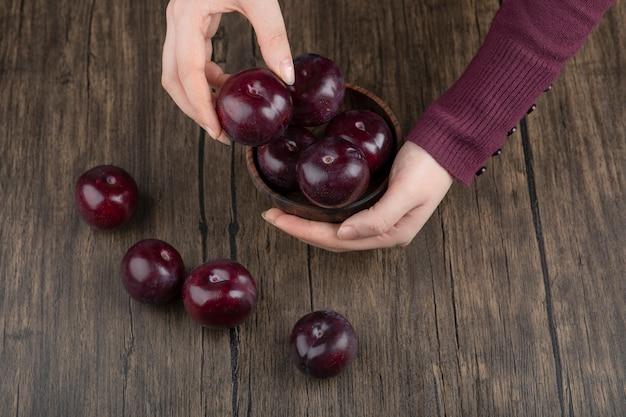 Vrouw handen met een houten kom met gezonde paarse pruimen.