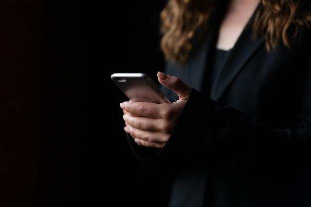 Vrouw handen met een smartphone op zwarte achtergrond