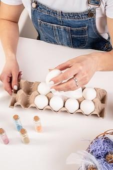 Vrouw handen met een wit ei klaar voor paasei kleuren bovenaanzicht