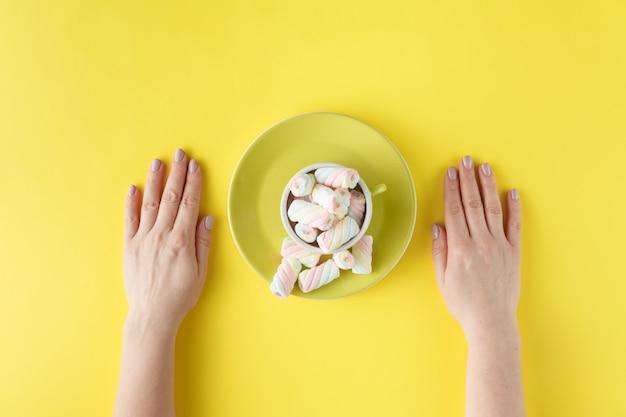 Vrouw handen met gedraaide marshmallow op levendige achtergrond