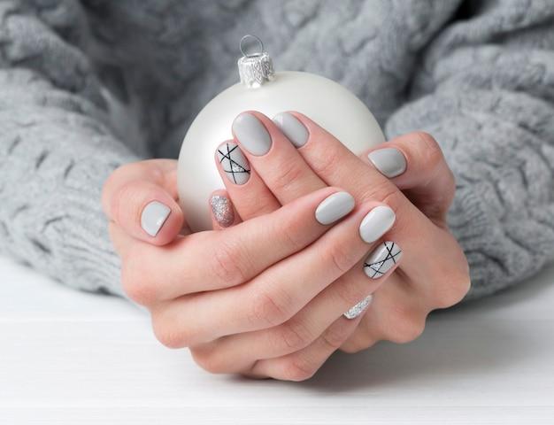 Vrouw handen met geometrische manicure nagel ontwerp in gezellige trui