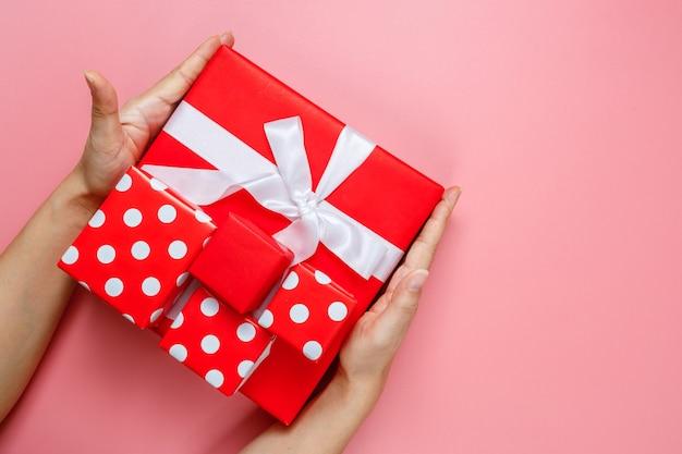 Vrouw handen met geschenken verpakt en versierd met strik