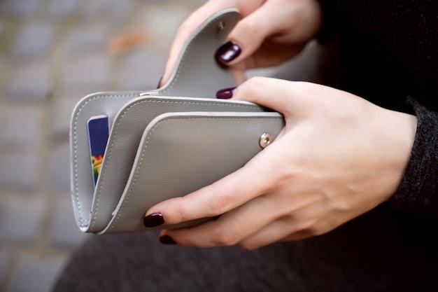 Vrouw handen met grijze portemonnee portemonnee geld creditcards