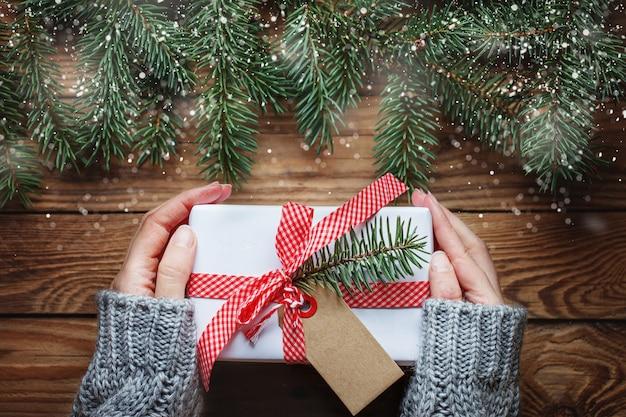 Vrouw handen met kerst geschenkdoos in papier wit met label voor tekst