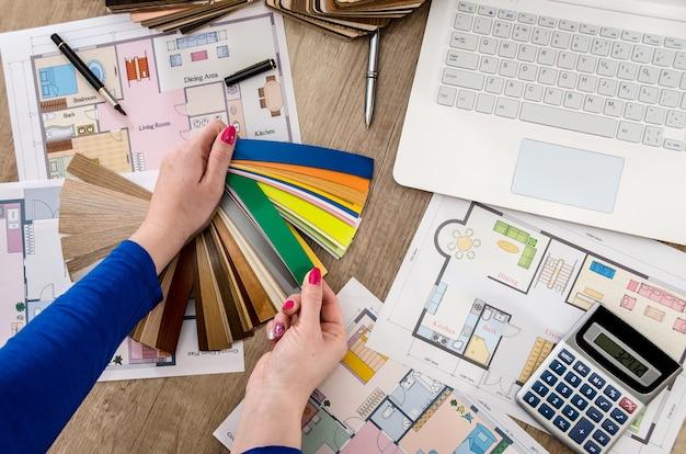 Vrouw handen met kleur monsters huis plan laptop en rekenmachine