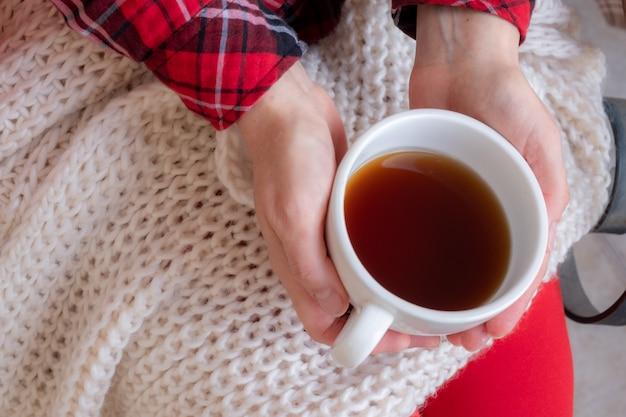 Vrouw handen met kopjes thee of koffie gekleed in rode en witte feestelijke kleding.