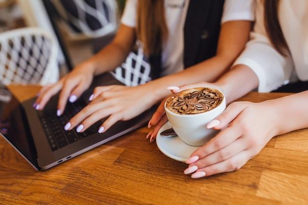 Vrouw handen met latte tijdens het werk op kantoor